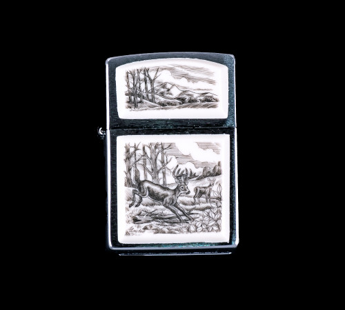 """This is a stunning originally hand etched Eco-Ivory Scrimshaw Jumping Deer Designed Zippo! The top of the flip lighter has a a Mountain Range with Tree's design. The Zippo is a Brushed Chrome finish. Each lighter has a bottom stamp signifying the year it was made, is refillable. All windproof lighters are American made in Bradford, PA factory and come packaged in a gift box. This is part of the Save the Elephant Collection and was originally hand etched by Linda Layden. The SKU is NC 54 - 110.  The Zippo Lighter is 2.24"""" x 1.51"""" x 0.59"""". It weighs 2.04 oz."""