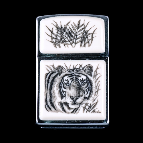 """This is a beautiful originally hand etched Eco-Ivory Scrimshaw Tiger Designed Zippo! The top of the flip lighter has a Jungle Fern design. The Zippo is a Brushed Chrome finish. Each lighter has a bottom stamp signifying the year it was made, is refillable. All windproof lighters are American made in Bradford, PA factory and come packaged in a gift box. This is part of the Save the Elephant Collection and was originally hand etched by Linda Layden. The SKU is NC 54 - 135.  The Zippo Lighter is 2.24"""" x 1.51"""" x 0.59"""". It weighs 2.04 oz."""