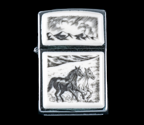 """This is a unique originally hand etched Eco-Ivory Scrimshaw Galloping Horses Designed Zippo! The top of the flip lighter has a Mountain design. The Zippo is a Brushed Chrome finish. Each lighter has a bottom stamp signifying the year it was made, is refillable. All windproof lighters are American made in Bradford, PA factory and come packaged in a gift box. This is part of the Save the Elephant Collection and was originally hand etched by Linda Layden. The SKU is NC 54 - 140.  The Zippo Lighter is 2.24"""" x 1.51"""" x 0.59"""". It weighs 2.04 oz."""