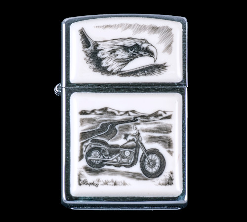 """This is a unique originally hand etched Eco-Ivory Scrimshaw Motorcycle Designed Zippo! The top of the flip lighter has a Eagle Face design. The Zippo is a Brushed Chrome finish. Each lighter has a bottom stamp signifying the year it was made, is refillable. All windproof lighters are American made in Bradford, PA factory and come packaged in a gift box. This is part of the Save the Elephant Collection and was originally hand etched by Linda Layden. The SKU is NC 54 - 210.  The Zippo Lighter is 2.24"""" x 1.51"""" x 0.59"""". It weighs 2.04 oz."""