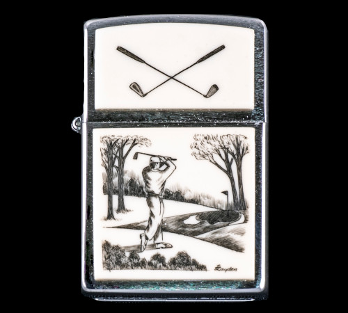 """This is a beautiful originally hand etched Eco-Ivory Scrimshaw Golfer Designed Zippo! The top of the flip lighter has Crossed Golf Clubs design. The Zippo is a Brushed Chrome finish. Each lighter has a bottom stamp signifying the year it was made, is refillable. All windproof lighters are American made in Bradford, PA factory and come packaged in a gift box. This is part of the Save the Elephant Collection and was originally hand etched by Linda Layden. The SKU is NC 54 - 205.  The Zippo Lighter is 2.24"""" x 1.51"""" x 0.59"""". It weighs 2.04 oz."""