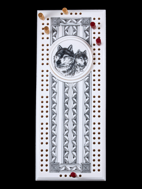 """This wonderful two person and our two team cribbage boards is a beautiful accent piece for your home or take it on the road for use as a travel cribbage board. With the magnet holding the center piece and pegs in place it is a stunning travel cribbage board.  This is a unique originally hand etched Dual Wolf Face Eco - Ivory Scrimshaw Cribbage Board! The center circular piece has a magnet holding it in place. Pushing on the base of the piece pops the Large round off the board, where the pegs are stored. All cribbage boards come with 3 red and 3 white/yellow wooden pegs.  The cribbage board itself is made for two players or teams. The board has a native geometric design that was originally hand etched. The large round piece has a magned on the back to keep it secured to the board and store the pegs. The pegs are made of wood. This is part of the Save the Elephant Collection and was originally hand etched by Linda Layden. The SKU is NC 53 - 103.  The Cribbage Board is 8.50"""" x 3.46"""" x 0.46"""". It weighs 11.28 oz."""