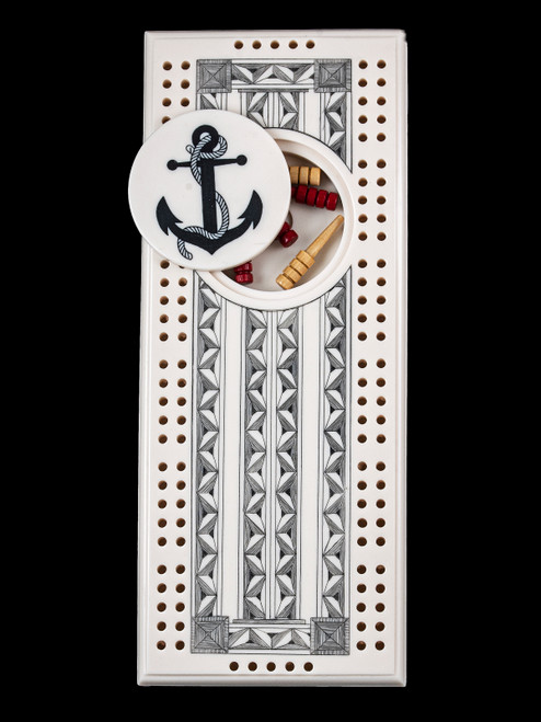 This wonderful two person and our two team cribbage boards is a beautiful accent piece for your home or take it on the road for use as a travel cribbage board.  With the magnet holding the center piece and pegs in place it is a stunning travel cribbage board.   This is a unique originally hand etched Anchor Design Eco - Ivory Scrimshaw Cribbage Board!  The center circular piece has a magnet holding it in place.  Pushing on the base of the piece pops the Large round off the board, where the pegs are stored.  All cribbage boards come with 3 red and 3 white/yellow wooden pegs.   The cribbage board itself is made for two players or teams.  The board has a native geometric design that was originally hand etched.  The large round piece has a magnet on the back to keep it secured to the board and store the pegs.  The pegs are made of wood.  This is part of the Save the Elephant Collection and was originally hand etched by Linda Layden.  The SKU is NC 53 - 416A.