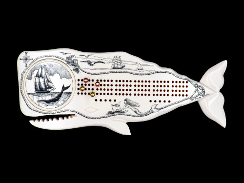 """Ship and Whale Cribbage Board Whale Shaped.  This wonderful two person and our two team cribbage boards is a beautiful accent piece for your home or take it on the road for use as a travel cribbage board. With the magnet holding the center piece and pegs in place it is a stunning travel cribbage board that will keep the pegs in place.  This is a beautiful originally hand etched Ship and Whale Eco - Ivory Scrimshaw Whale Shaped Cribbage Board! The board itself is shaped of a Humpback Whale. The center circular piece has a magnet holding it in place. Pushing on the base of the piece pops the Large round off the board, where the pegs are stored. All cribbage boards come with 3 Silver and 3 Gold Metal pegs.  The cribbage board itself is made for two players or teams. The board has a native geometric design that was originally hand etched. The large round piece has a magnet on the back to keep it secured to the board and store the pegs. The pegs are made of wood. This is part of the Save the Elephant Collection and was originally hand etched by Linda Layden. The SKU is NC 53 - 403.  The Cribbage Board is 9.00"""" x 3.54"""" x 0.48"""". It weighs 7.35 oz."""