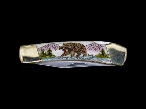 """LB 5 102B Scrimshaw Collection Bear with Trout Pocket Knife.  This stunning hand etched Colored Bear eating a trout along a river design on a 440 Stainless Steel Blade LB 5 Knife. This beautiful knife is part of the Scrimshaw Collection, with those words laser engraved into the blade. The LB 5 knifes come with the pictured leather sheath and each scale is made with Bovine Bone. The LB 5 Knife has bolsters and shackle that are nickel silver with brass pins and liner. It is a lock blade knife and a very useful pocket knife. The dimensions of the LB 5 Pocket Knife with the blade closed are 3.71"""" x 0.90"""" x 0.39"""". The blade itself is approximately 2.80"""" making the width of the knife with an open blade 6.51"""". The SKU is LB-5 102B.  The scrimshaw is inked with colored india ink and sealed with renaissance wax, which is used by museums for antique restoration. It also helps bring out the beauty of the artwork as well as in the cow bone. The knife is water resistant, but not waterproof."""