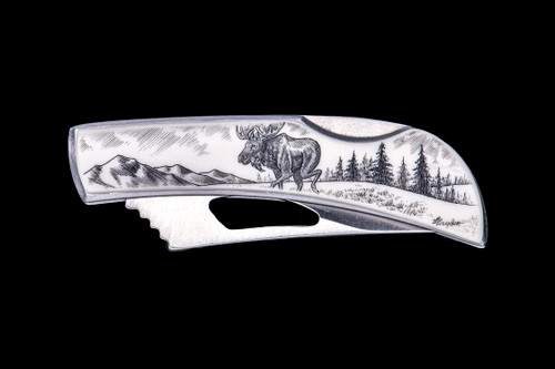 "Moose Silver Hawk Knife.  This beautifully originally hand etched Eco-Ivory Moose design on a Stainless Steel Silver Hawk Knife.  The back of the knife has a belt clip and all the knifes come with the pictured sheath.  It is a lock blade knife and a useful pocket knife. The artwork was originally hand etched by Linda Layden.  The dimensions of the Silver Hawk knife with the blade closed are 3.00"" x 0.96"" x 0.55"".  The blade itself is approximately 2.35"" making the width of the knife with an open blade 5.35"".  The SKU is NC 14 - 119."