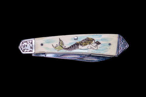 """This stunning hand etched Colored Mermaid design on a 440 Stainless Steel Dual Blade Knife. The knife design is similar to the Shrade 2222 knife. This beautiful knife is part of the Scrimshaw Collection, with those words laser engraved into the blade. The DB 2222 knifes come with the pictured leather sheath and each scale is made with Bovine Bone. The DB 2222 knife has bolsters that are nickel silver with brass pins and liner. It is a dual blade knife and a very useful pocket knife. The dimensions of the DB 2222 Pocket Knife with the blade closed are 3.48"""" x 0.90"""" x 0.58"""". The large blade itself is approximately 2.67"""" making the width of the knife with an open blades 6.15"""". The small blades length is approximately 1.90"""". The SKU is DB 2222 - 139C.   The scrimshaw is inked with colored india ink and sealed with renaissance wax, which is used by museums for antique restoration. It also helps bring out the beauty of the artwork as well as in the cow bone. The knife is water resistant, but not waterproof."""