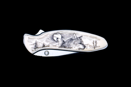 """NC 1600 Chive Wolf Pocket Knife.  This stunning originally hand etched Wolf design on a Kershaw 1600 Chive Speedsafe Assisted Opening Pocket Knife. The back of the knife has a belt clip/ money clip and the knifes come with the pictured sheath. It is a lock blade knife and a useful pocket knife. The artwork was originally hand etched by Linda Layden. The dimensions of the Kershaw 1600 Chive Pocket knife with the blade closed are 2.95"""" x 0.92"""" x 0.53"""". The blade itself is approximately 1.9"""" making the width of the knife with an open blade 4.85"""". The SKU is NC 1600 - 105.  This unique etching has a wolf howling at the moon in the background, with a face of another wolf in the foreground. This design is set in a mountainess region.  Linda Layden has been making beautiful works of art in the scrimshaw field for over 40 years. Originally a hobby that became a full time job. Her work can be found in gift shops, galleries and museums across the world."""