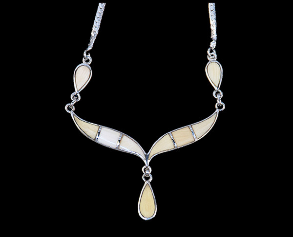 """This unique whale tail with Teardrop Mammoth ivory shaped whale tail is inlayed into a sterling silver pendant.  This pendant comes with an 18"""" Sterling Silver chain.  The dimensions of the mammoth pendant tusk is approximately 2.25"""" x 1.7""""."""