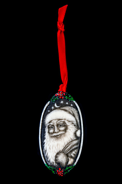 "This is a beautiful double sided ornament with a Santa theme.  This is part of the incredible line of Mossup Valley Designs that we carry, with the wonderful artist Rachel Badeau.  The dimensions of the ornament are 3.28"" x 1.61"".  The SKU is MVD ORN 9.  On this double sided ornament, Christmas designs are prominently featured on both sides.  On one side there is closeup of Santa's face while holding a bag of toys design.  On the other side of the ornament, a North Pole Design.  Rachel Badeau has been etching and engraving in a variety of media for over thirty years.  Her work, characterized by fine line and intricate detail, attempts to touch the hearts and emotions of others.  All while reflecting her love of animals, nature and the human spirit."