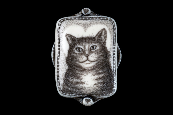"""This beautiful originally hand etched Sweet Heart Cat designed pin/pendant. The backing of this piece has the findings to be a pin, as well as a pendant. They come with an 18"""" Silver Plated Chain. This is part of the incredible line of Mossup Valley Designs that we carry, with the wonderful artist Rachel Badeau. The dimensions of the necklace are 1.24"""" x 1.77"""" x 0.36"""". The SKU is MVD PN 16.  Rachel Badeau has been etching and engraving in a variety of media for over thirty years. Her work, characterized by fine line and intricate detail, attempts to touch the hearts and emotions of others. All while reflecting her love of animals, nature and the human spirit.  The resin scrimshaw piece is originally hand etched by Rachel Badeau. We make a mold of the original piece and do an open cast pour of our resin mixture. The pieces are removed from the mold and sanded and inked."""