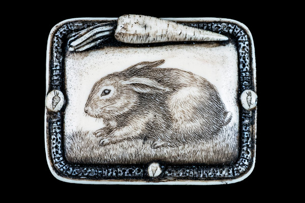 """This distinct originally hand etched Rabbit designed pin/pendant. This piece has a bunny with a carrot on top. The backing of this piece has the findings to be a pin, as well as a pendant. They come with an 18"""" Silver Plated Chain. This is part of the incredible line of Mossup Valley Designs that we carry, with the wonderful artist Rachel Badeau. The dimensions of the necklace are 1.77"""" x 1.43"""" x 0.50"""". The SKU is MVD PN 40.  Rachel Badeau has been etching and engraving in a variety of media for over thirty years. Her work, characterized by fine line and intricate detail, attempts to touch the hearts and emotions of others. All while reflecting her love of animals, nature and the human spirit.  The resin scrimshaw piece is originally hand etched by Rachel Badeau. We make a mold of the original piece and do an open cast pour of our resin mixture. The pieces are removed from the mold and sanded and inked."""