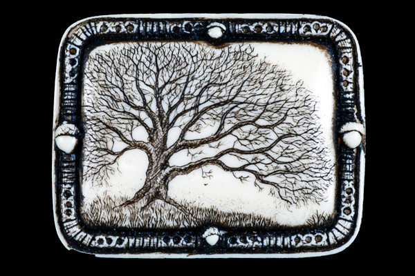 """This distinct originally hand etched Woodland designed pin/pendant. The Woodland design features an Oak Tree. The backing of this piece has the findings to be a pin, as well as a pendant. They come with an 18"""" Silver Plated Chain. This is part of the incredible line of Mossup Valley Designs that we carry, with the wonderful artist Rachel Badeau. The dimensions of the necklace are 1.82"""" x 1.41"""" x 0.43"""". The SKU is MVD PN 11.  Rachel Badeau has been etching and engraving in a variety of media for over thirty years. Her work, characterized by fine line and intricate detail, attempts to touch the hearts and emotions of others. All while reflecting her love of animals, nature and the human spirit.  The resin scrimshaw piece is originally hand etched by Rachel Badeau. We make a mold of the original piece and do an open cast pour of our resin mixture. The pieces are removed from the mold and sanded and inked."""