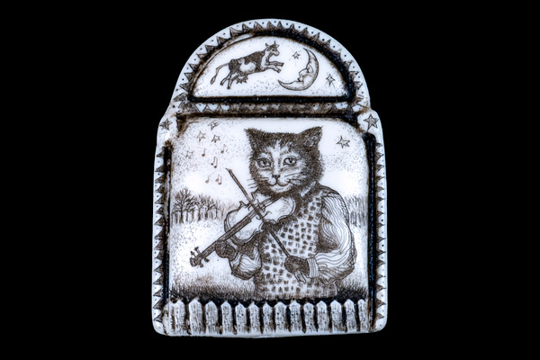 """This distinct originally hand etched Hey Diddle Diddle designed pin/pendant. The design comes with a cat playing a fiddle with a cow jumping over the moon on top. They come with an 18"""" Silver Plated Chain. This is part of the incredible line of Mossup Valley Designs that we carry, with the wonderful artist Rachel Badeau. The dimensions of the necklace are 1.24"""" x 1.71"""" x 0.44"""". The SKU is MVD PN 48.  Rachel Badeau has been etching and engraving in a variety of media for over thirty years. Her work, characterized by fine line and intricate detail, attempts to touch the hearts and emotions of others. All while reflecting her love of animals, nature and the human spirit.  The resin scrimshaw piece is originally hand etched by Rachel Badeau. We make a mold of the original piece and do an open cast pour of our resin mixture. The pieces are removed from the mold and sanded and inked."""