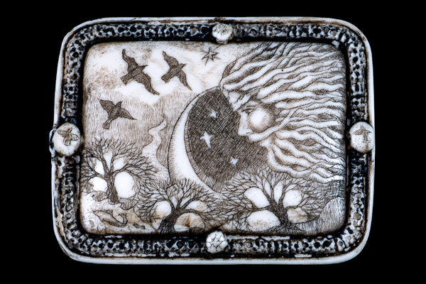 """This distinct originally hand etched North Wind designed pin/pendant. They come with an 18"""" Silver Plated Chain. This is part of the incredible line of Mossup Valley Designs that we carry, with the wonderful artist Rachel Badeau. The dimensions of the necklace are 1.80"""" x 1.41"""" x 0.37"""". The SKU is MVD PN 48.  Rachel Badeau has been etching and engraving in a variety of media for over thirty years. Her work, characterized by fine line and intricate detail, attempts to touch the hearts and emotions of others. All while reflecting her love of animals, nature and the human spirit.  The resin scrimshaw piece is originally hand etched by Rachel Badeau. We make a mold of the original piece and do an open cast pour of our resin mixture. The pieces are removed from the mold and sanded and inked."""