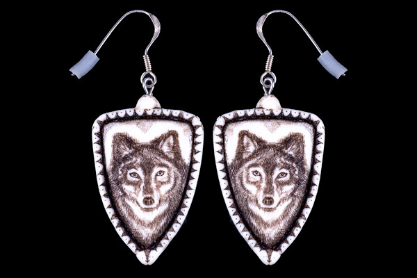"""This is a beautiful originally hand etched Wolf French Wire Earring set. This is part of the incredible line of Mossup Valley Designs that we carry, with the wonderful artist Rachel Badeau. All the earrings come carded. The dimensions of the earrings are .90"""" x 1.36"""" x 0.18"""". The SKU is MVD ER 01.  Rachel Badeau has been etching and engraving in a variety of media for over thirty years. Her work, characterized by fine line and intricate detail, attempts to touch the hearts and emotions of others. All while reflecting her love of animals, nature and the human spirit.  The resin scrimshaw piece is originally hand etched by Rachel Badeau. We make a mold of the original piece and do an open cast pour of our resin mixture. The pieces are removed from the mold and sanded and inked."""