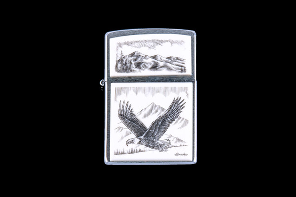 """This is a beautiful originally hand etched Eco-Ivory Scrimshaw Flying Eagle designed Zippo Lighter! The top of the flip lighter has a a Mountain Skyline Top piece. The Zippo is a Brushed Chrome finish. Each lighter has a bottom stamp signifying the year it was made, is refillable. All windproof lighters are American made in Bradford, PA factory and come packaged in a gift box. This is part of the Save the Elephant Collection and was originally hand etched by Linda Layden. The SKU is NC 54 - 162A.  The Zippo Lighter is 2.24"""" x 1.51"""" x 0.59"""". It weighs 2.04 oz."""