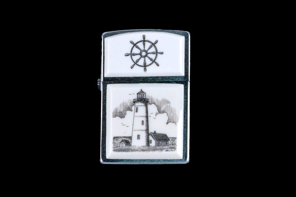 "This is a stunning Nautical originally hand etched Eco-Ivory Scrimshaw Lighthouse designed Zippo Lighter! The top of the flip lighter has a a Ship Wheel piece.  The Zippo is a Brushed Chrome finish. Each lighter has a bottom stamp signifying the year it was made, is refillable. All windproof lighters are American made in Bradford, PA factory and come packaged in a gift box.  This is part of the Save the Elephant Collection and was originally hand etched by Linda Layden. The SKU is NC 54 - 223.  The Zippo Lighter is 2.24"" x 1.51"" x 0.59"".  It weighs 2.04 oz."