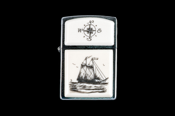 """This is a incredible Nautical Style Eco-Ivory Scrimshaw Schooner Ship designed Zippo Lighter! The top of the flip lighter has a Compass Rose design. The Zippo is a Brushed Chrome finish. Each lighter has a bottom stamp signifying the year it was made, is refillable. All windproof lighters are American made in Bradford, PA factory and come packaged in a gift box. This is part of the Save the Elephant Collection and was originally hand etched by Bill Feeney. The SKU is NC 54 - 450.  The Zippo Lighter is 2.24"""" x 1.51"""" x 0.59"""". It weighs 2.04 oz."""