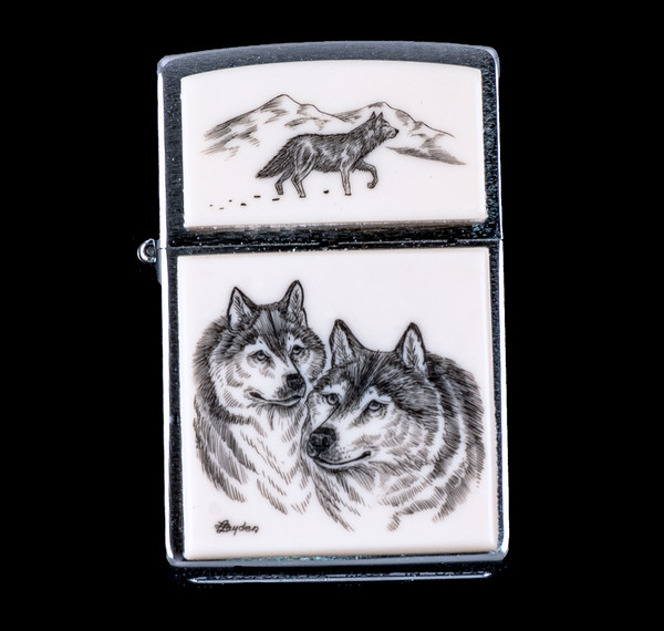 """This is a beautiful originally hand etched Eco-Ivory Scrimshaw Double Wolf Designed Zippo! The top of the flip lighter has a walking Wolf design. The Zippo is a Brushed Chrome finish. Each lighter has a bottom stamp signifying the year it was made, is refillable. All windproof lighters are American made in Bradford, PA factory and come packaged in a gift box. This is part of the Save the Elephant Collection and was originally hand etched by Linda Layden. The SKU is NC 54 - 146.  The Zippo Lighter is 2.24"""" x 1.51"""" x 0.59"""". It weighs 2.04 oz."""