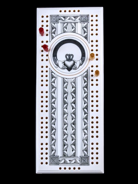 This wonderful two person and our two team cribbage boards is a beautiful accent piece for your home or take it on the road for use as a travel cribbage board. With the magnet holding the center piece and pegs in place it is a stunning travel cribbage board.  This is a stunning originally hand etched Claddagh Eco - Ivory Scrimshaw Cribbage Board! The Claddagh Ring design is a traditional Irish design that represents love, loyalty, and friendship! The hands represent friendship, the heart represents love, and the crown represents loyalty.The center circular piece has a magnet holding it in place. Pushing on the base of the piece pops the Large round off the board, where the pegs are stored. All cribbage boards come with 3 red and 3 white/yellow wooden pegs.  The cribbage board itself is made for two players or teams. The board has a native geometric design that was originally hand etched. The large round piece has a magnet on the back to keep it secured to the board and store the pegs. The pegs are made of wood. This is part of the Save the Elephant Collection and was originally hand etched by Linda Layden. The SKU is NC 53 - 178.