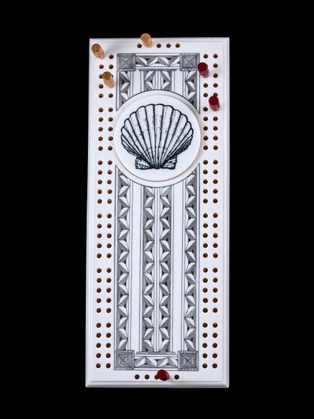 "This wonderful two person and our two team cribbage boards is a beautiful accent piece for your home or take it on the road for use as a travel cribbage board.  With the magnet holding the center piece and pegs in place it is a stunning travel cribbage board.   This is a beautiful originally hand etched Seashell Design Eco - Ivory Scrimshaw Cribbage Board!  The center circular piece has a magnet holding it in place.  Pushing on the base of the piece pops the Large round off the board, where the pegs are stored.  All cribbage boards come with 3 red and 3 white/yellow wooden pegs.   The cribbage board itself is made for two players or teams.  The board has a native geometric design that was originally hand etched.  The large round piece has a magnet on the back to keep it secured to the board and store the pegs.  The pegs are made of wood.  This is part of the Save the Elephant Collection and was originally hand etched by Linda Layden.  The SKU is NC 53 - 416SS.  The Cribbage Board is 8.50"" x 3.46"" x 0.46"".  It weighs 11.28 oz."