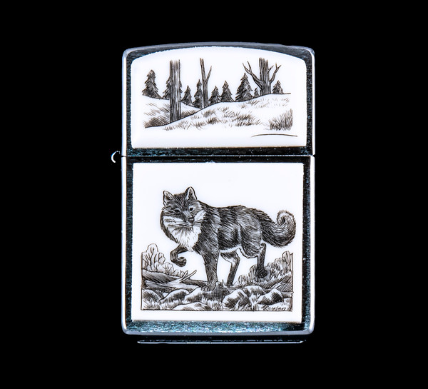 """This is a stunning originally hand etched Eco-Ivory Scrimshaw Fox Designed Zippo! The top of the flip lighter has a hills with tree design. The Zippo is a Brushed Chrome finish. Each lighter has a bottom stamp signifying the year it was made, is refillable. All windproof lighters are American made in Bradford, PA factory and come packaged in a gift box. This is part of the Save the Elephant Collection and was originally hand etched by Linda Layden. The SKU is NC 54 - 170.  The Zippo Lighter is 2.24"""" x 1.51"""" x 0.59"""". It weighs 2.04 oz."""
