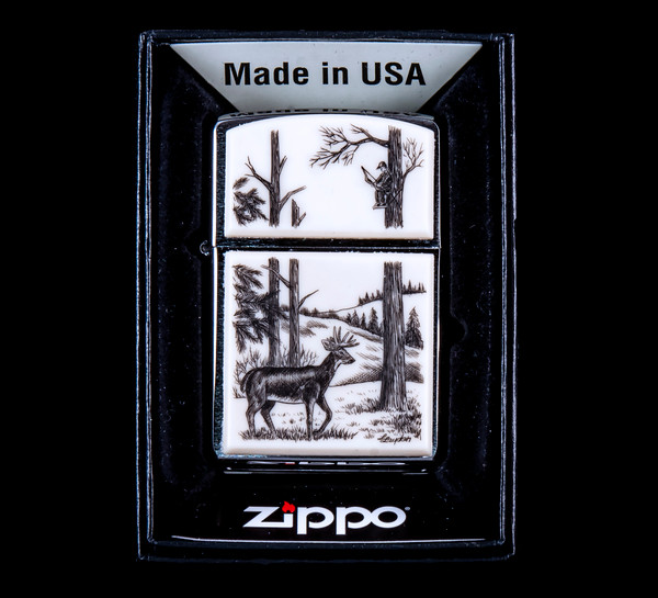 """This is a beautiful originally hand etched Eco-Ivory Scrimshaw Deer Designed Zippo! The top of the flip lighter has a bow hunter in a tree design. The Zippo is a Brushed Chrome finish. Each lighter has a bottom stamp signifying the year it was made, is refillable. All windproof lighters are American made in Bradford, PA factory and come packaged in a gift box. This is part of the Save the Elephant Collection and was originally hand etched by Linda Layden. The SKU is NC 54 - 112.  The Zippo Lighter is 2.24"""" x 1.51"""" x 0.59"""". It weighs 2.04 oz."""