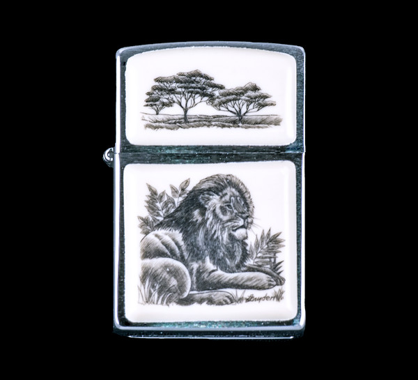 """This is a beautiful originally hand etched Eco-Ivory Scrimshaw Lion Designed Zippo! The top of the flip lighter has a tree design. The Zippo is a Brushed Chrome finish. Each lighter has a bottom stamp signifying the year it was made, is refillable. All windproof lighters are American made in Bradford, PA factory and come packaged in a gift box. This is part of the Save the Elephant Collection and was originally hand etched by Linda Layden. The SKU is NC 54 - 136.  The Zippo Lighter is 2.24"""" x 1.51"""" x 0.59"""". It weighs 2.04 oz."""