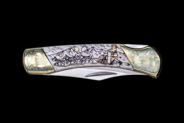 """Dog Sled LB3 Pocket Knife.  This stunning hand etched Colored Dog Sled design on a 440 Stainless Steel Blade LB 3 Knife. This beautiful knife is part of the Scrimshaw Collection, with those words laser engraved into the blade. The LB 3 knifes come with the pictured leather sheath and each scale is made with Bovine Bone. The LB 3 Knife has bolsters and shackle that are nickel silver with brass pins and liner. It is a lock blade knife and a very useful pocket knife. The dimensions of the LB 3 Pocket Knife with the blade closed are 2.97"""" x 0.76"""" x 0.31"""". The blade itself is approximately 2.21"""" making the width of the knife with an open blade 5.18"""". The SKU is LB-3 242C."""
