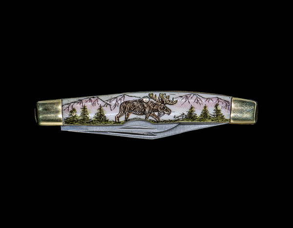 """Moose Dual Blade Pocket Knife.  This beautiful hand etched Moose design on a 440 Stainless Steel Dual Blade Knife. The moose is walking in the forrest in front of mountains. The knife design is similar to the Shrade 33 knife. This beautiful knife is part of the Scrimshaw Collection, with those words laser engraved into the blade. The DB 33 knifes come with the pictured leather sheath and each scale is made with Bovine Bone. The DB 33 Knife has bolsters that are nickel silver with brass pins and liner. It is a dual blade knife and a very useful pocket knife. The dimensions of the DB 33 Pocket Knife with the blade closed are 3.28"""" x 0.69"""" x 0.50"""". The large blade itself is approximately 2.45"""" making the width of the knife with an open blades 5.73"""". The small blades length is approximately 1.77"""". The SKU is DB 33 - 102C."""