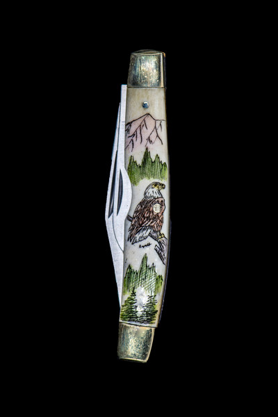 """Eagle Dual Blade Knife.  This stunning hand etched Eagle design on a 440 Stainless Steel Dual Blade Knife. The Eagle is perched on a tree with mountains in the background. The knife design is similar to the Shrade 33 knife. This beautiful knife is part of the Scrimshaw Collection, with those words laser engraved into the blade. The DB 33 knifes come with the pictured leather sheath and each scale is made with Bovine Bone. The DB 33 Knife has bolsters that are nickel silver with brass pins and liner. It is a dual blade knife and a very useful pocket knife. The dimensions of the DB 33 Pocket Knife with the blade closed are 3.28"""" x 0.69"""" x 0.50"""". The large blade itself is approximately 2.45"""" making the width of the knife with an open blades 5.73"""". The small blades length is approximately 1.77"""". The SKU is DB 33 - 133VC."""