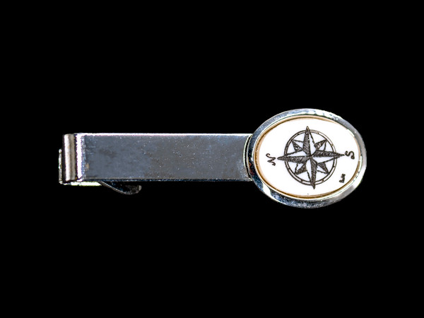 """Compass Rose Tie Bar NC 87B - 149.  This stunning hand etched Compass Rose design looks beautiful on the tie bar. The Tie Bar is made of solid brass and made in the USA. It has a Rhodium finish that gives it the unique silver look. It is a very durable finish. This unique Compass Rose Tie Bar weighs 3.5 ounces. The dimensions are 2.08"""" x .66""""x .65"""".  The item number is NC 87B - 149."""