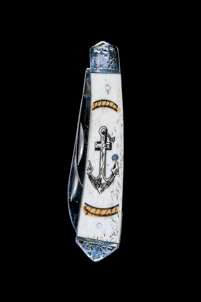 """DB 2222 602VC Anchor Design.  This beautiful hand etched Vertical Colored Anchor scene on a 440 Stainless Steel Dual Blade Knife. The knife design is similar to the Shrade 2222 knife. This beautiful knife is part of the Scrimshaw Collection, with those words laser engraved into the blade. The DB 2222 knifes come with the pictured leather sheath and each scale is made with Bovine Bone. The DB 2222 knife has bolsters that are nickel silver with brass pins and liner. It is a dual blade knife and a very useful pocket knife. The dimensions of the DB 2222 Pocket Knife with the blade closed are 3.48"""" x 0.90"""" x 0.58"""". The large blade itself is approximately 2.67"""" making the width of the knife with an open blades 6.15"""". The small blades length is approximately 1.90"""". The SKU is DB 2222 - 602VC.  The scrimshaw is inked with colored india ink and sealed with renaissance wax, which is used by museums for antique restoration. It also helps bring out the beauty of the artwork as well as in the cow bone. The knife is water resistant, but not waterproof."""