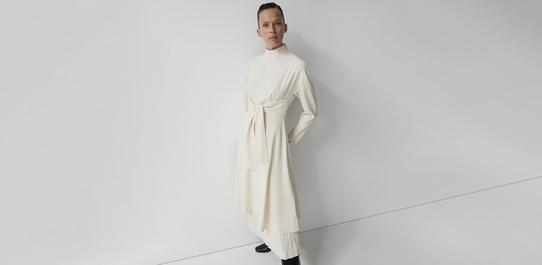 One of our designer dresses, a long-sleeved polyester in a beige colour dress with strip detail and central knot and mandarin collar.
