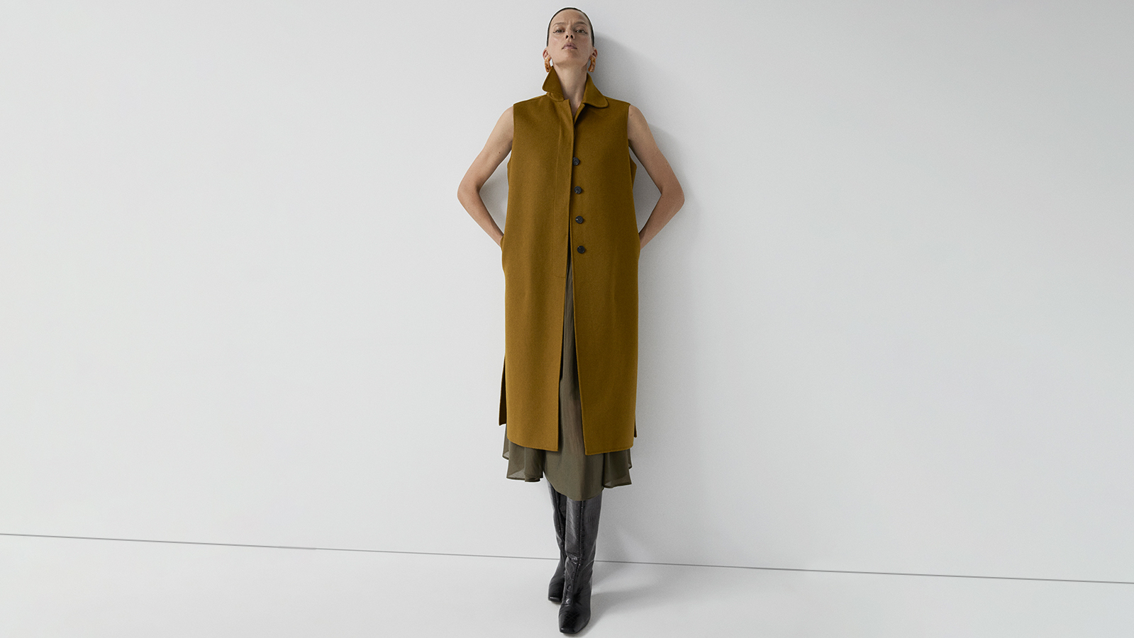 Designer coat crafted from a merino wool blend. It features shirt collar, buttons closure with flap, two pockets and side slits.