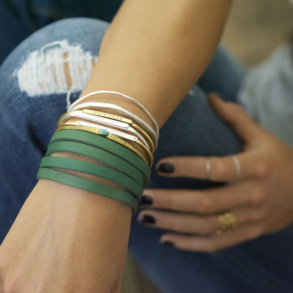 Brass thin cuff with turquoise inset stone, as part of a stack.