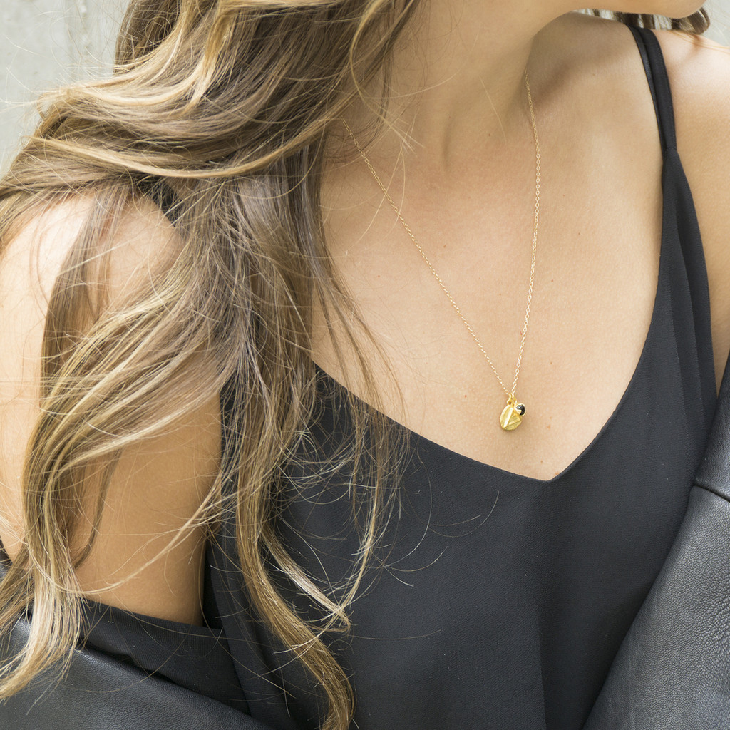 gold 'explore' charm necklace with black onyx stone detail