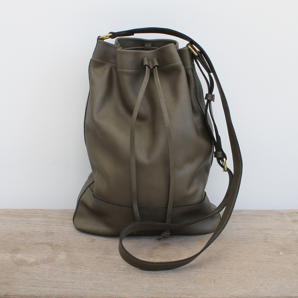 grey leather handbag with drawstring strap and adjustable straps