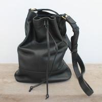 black leather handbag with drawstring strap and adjustable straps