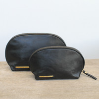 Small and large pouches with 'escape the ordinary' and 'take more detours' brass plates