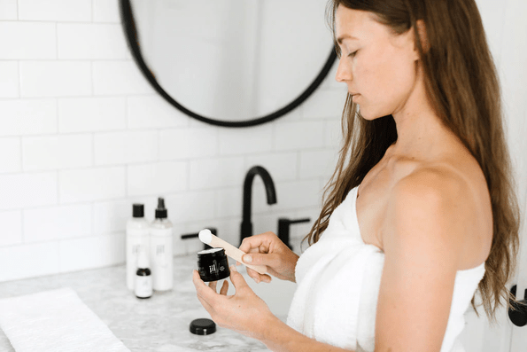 woman in a towel using a lotion in a bathroom