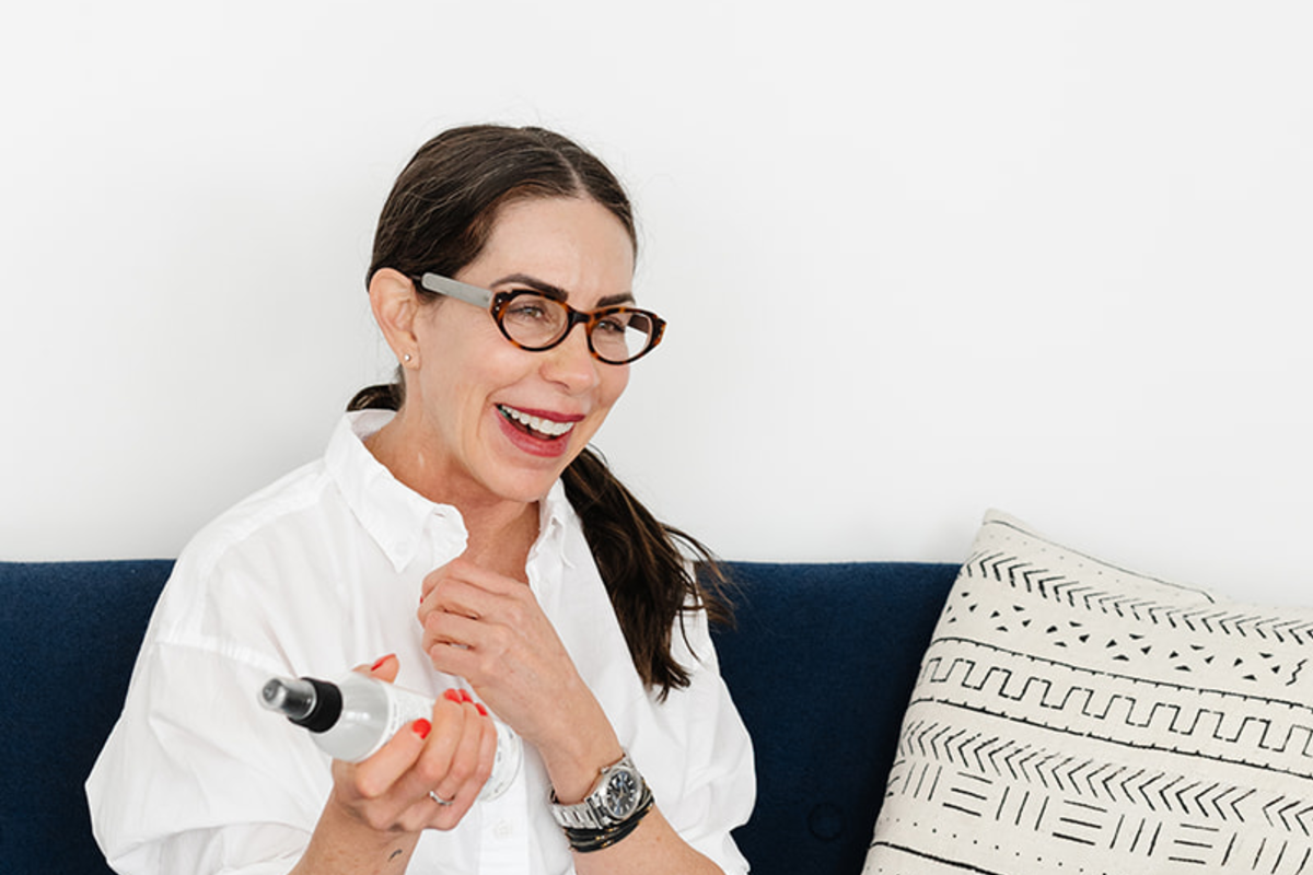 woman smiling sitting on a couch holding a beauty product bottle