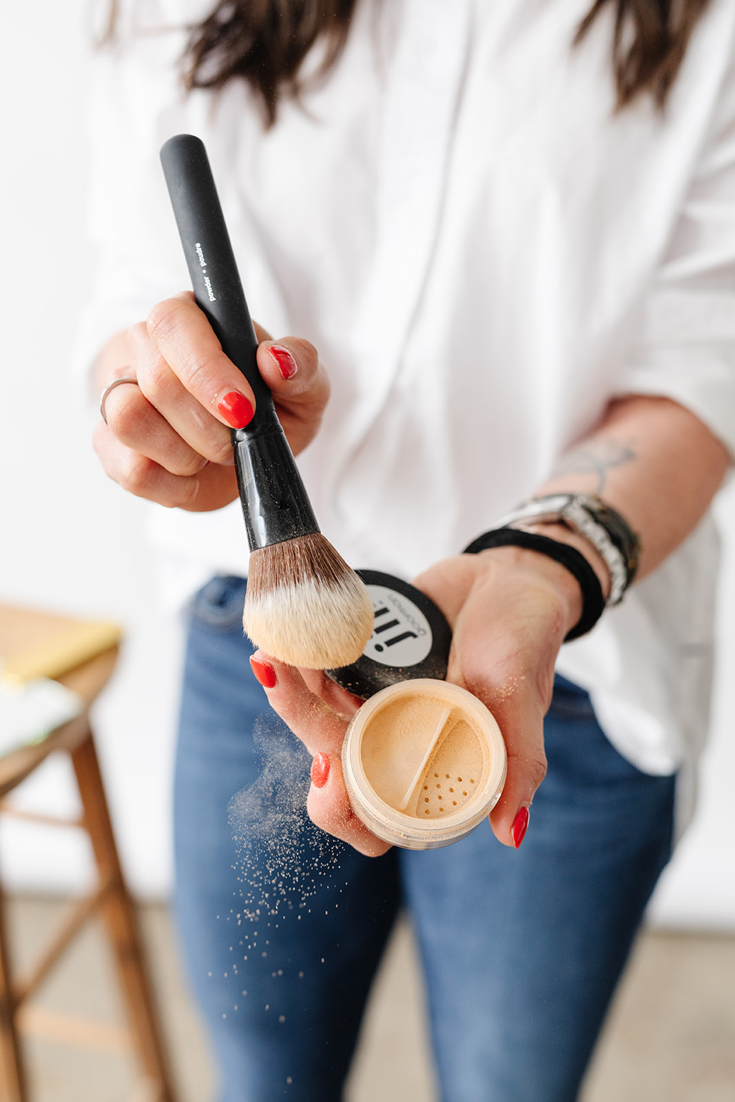close up of a woman holding powder makeup with a brush