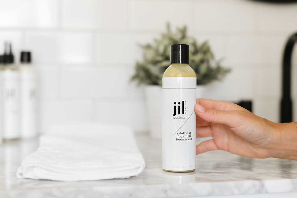 close up of a product bottle on a counter next to a towel and a hand touching the bottle