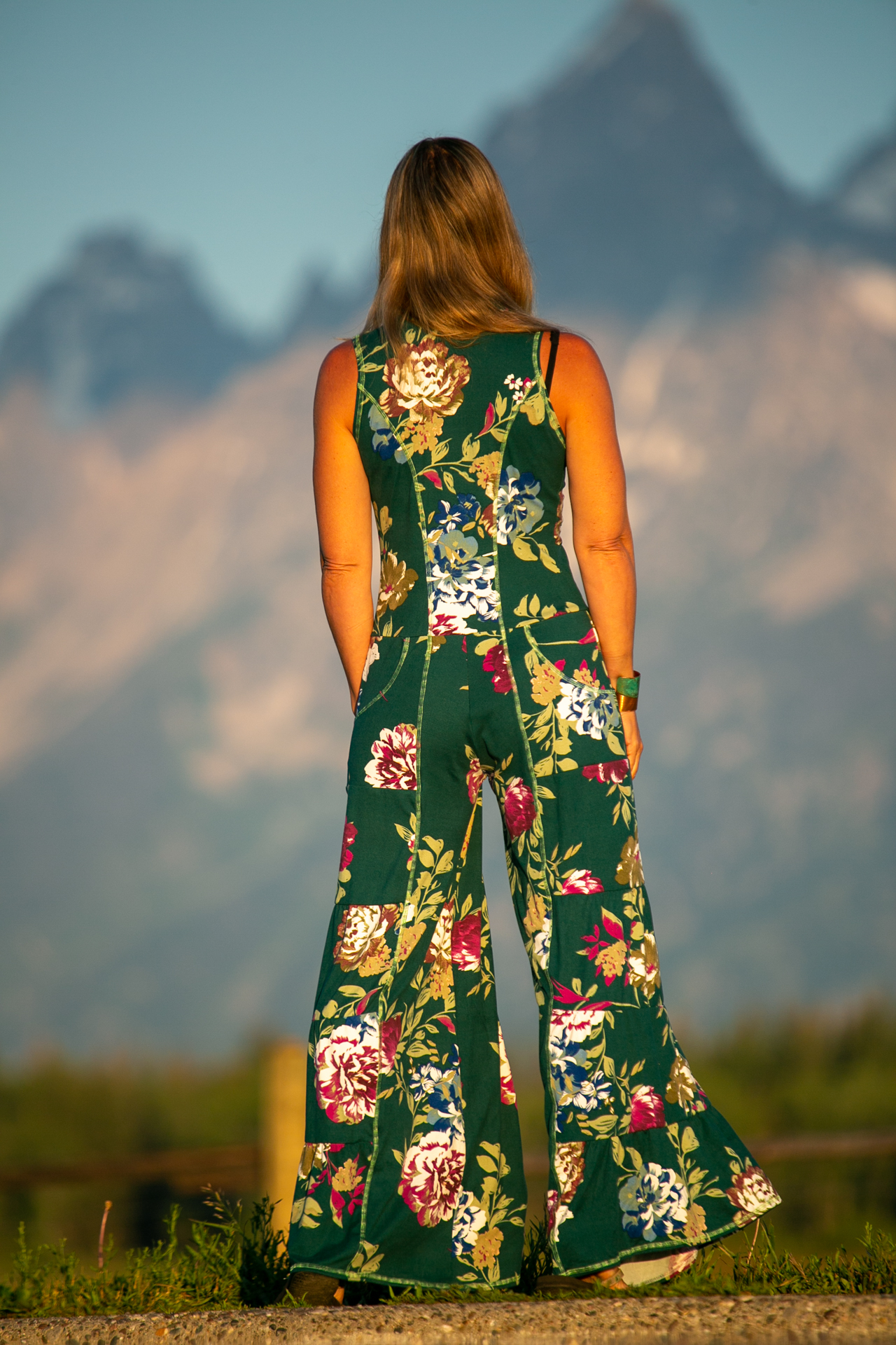 Fashion designer Autumn Teneyl wearing a boho style one piece jumpsuit in the mountains.