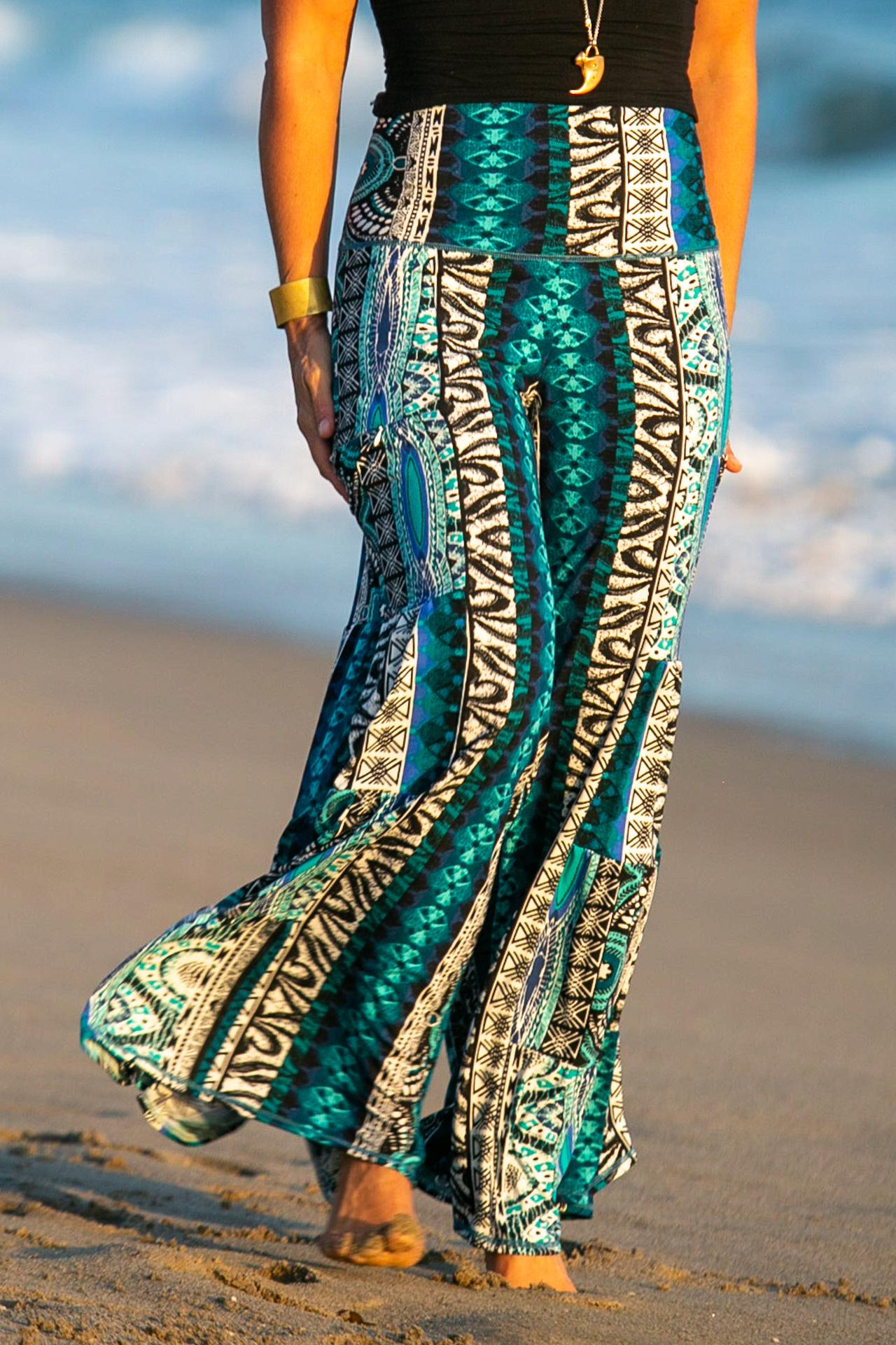 Fashion designer Autumn Teneyl walking at the beach wearing boho  pants with zippered pockets.