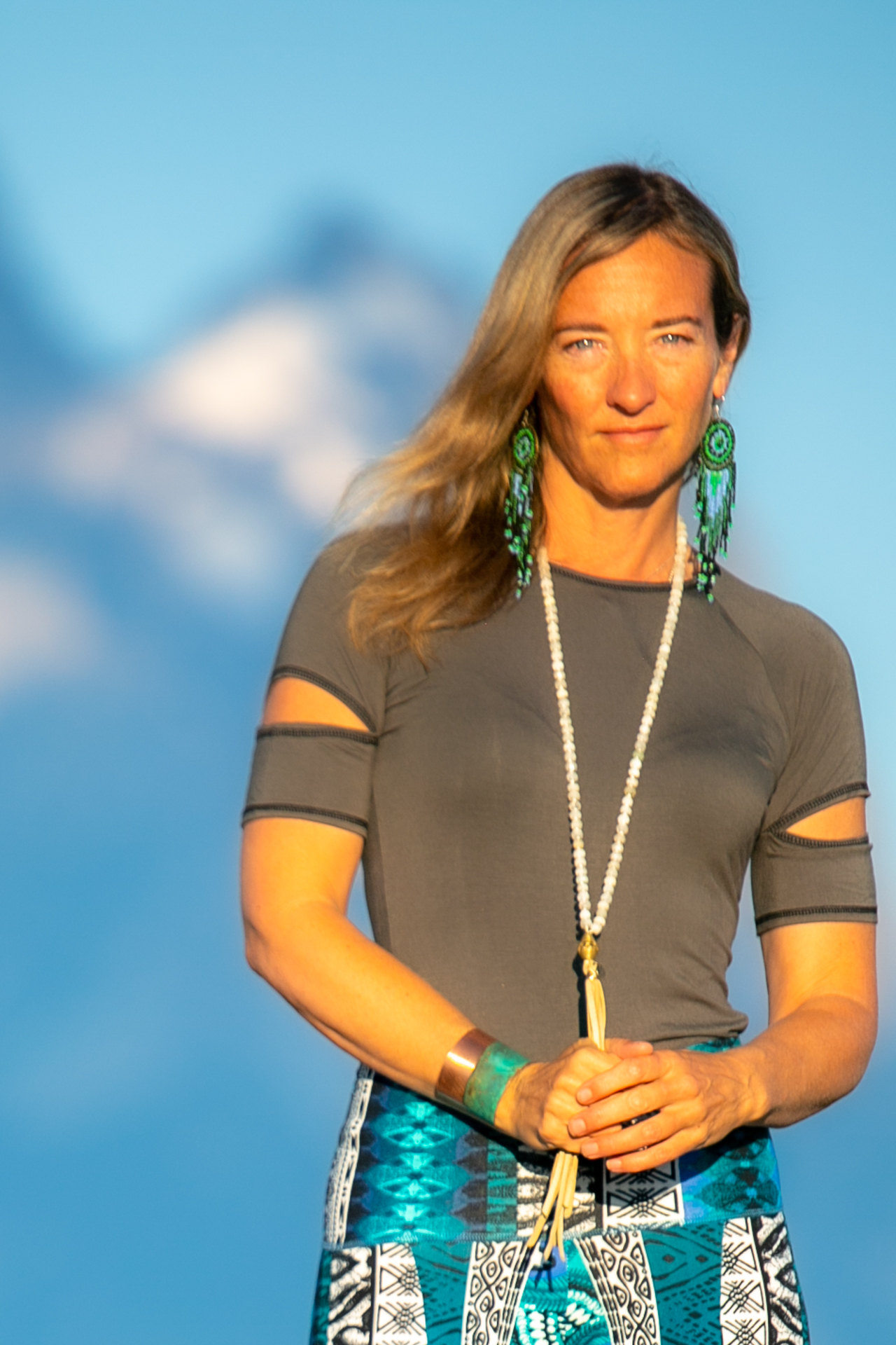 Fashion designer Autumn Teneyl wearing  short sleeved top in the Teton Mountains in Wyoming.