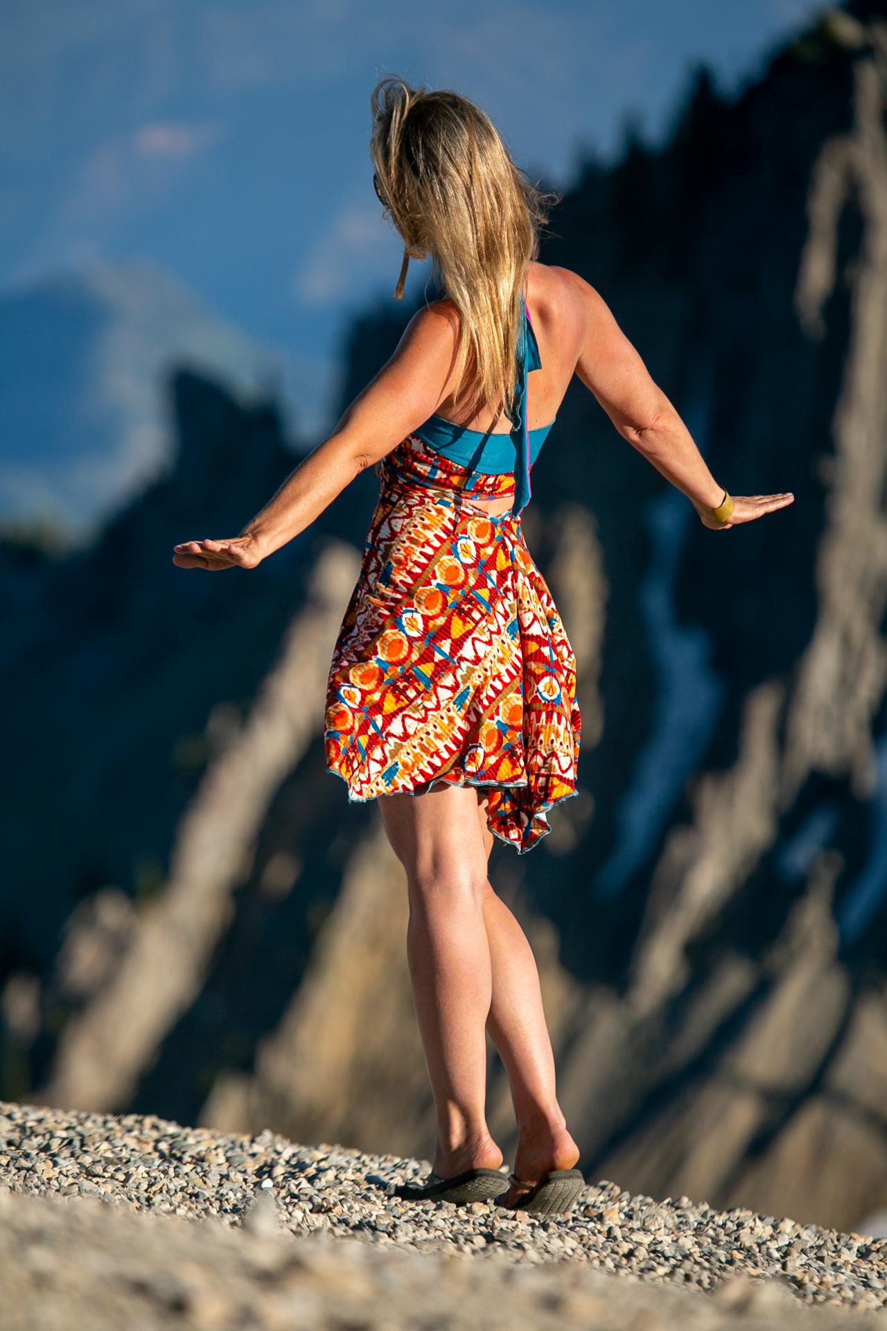 En trend fashion designer Autumn Teneyl wearing a festive halter dress on top on a California mountain.