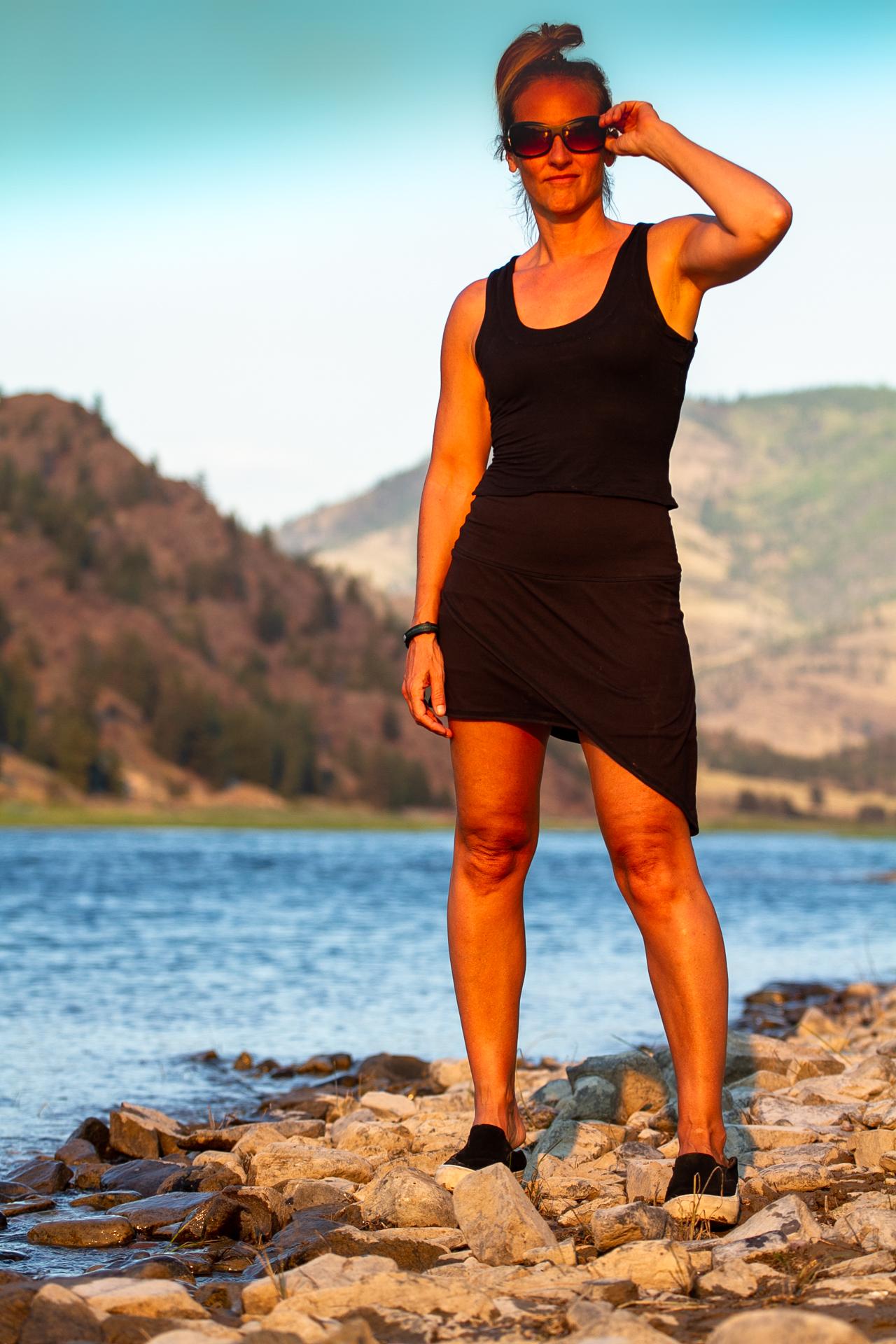 Fashion Designer Autumn Teneyl wearing a black skirt by a beautiful lake